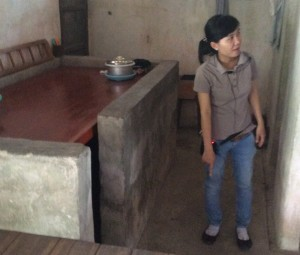 Tam, a Mekong River tour guide, stands by a bomb shelter in a farm house in Long An Province, now at peace.